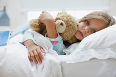 stock-photo-24414322-sick-girl-laying-in-bed-with-teddy-bear