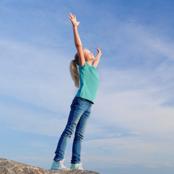 Relaxed girl breathing fresh air raising arms over blue sky at summer. Dreaming, freedom and traveling concept.